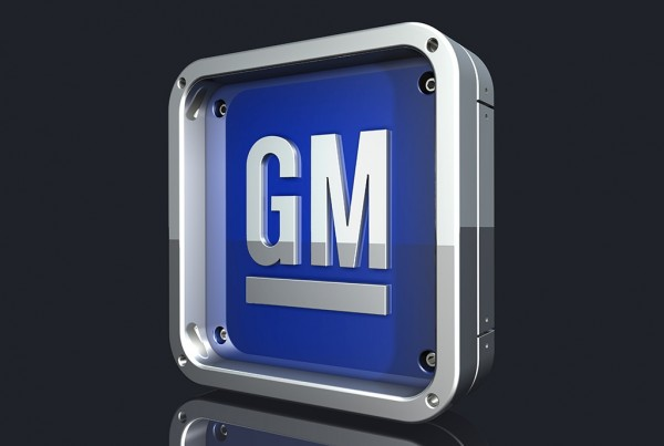 3d rendering of a large chrome and blue General Motors logo over a dark gray reflective surface